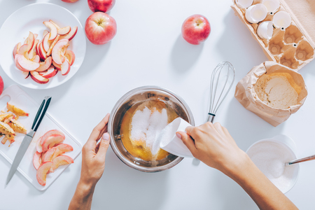 Process of making apple pie, top view. White table with ingredients for dough, cut and whole fruit. In the center female hand adding sugar to raw eggs to whisk.