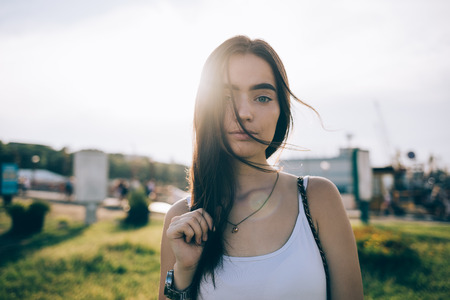 Portrait of stunning young woman wearing white top looking at camera when sun shine from behind. Girl with long brown hair and blue eyes posing in the city park at sunny summer day.