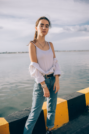 Portrait of beautiful girl standing near the sea at sunny summer day. Teen female wearing boyfriend jeans and white top posing at city port against black-yellow border.