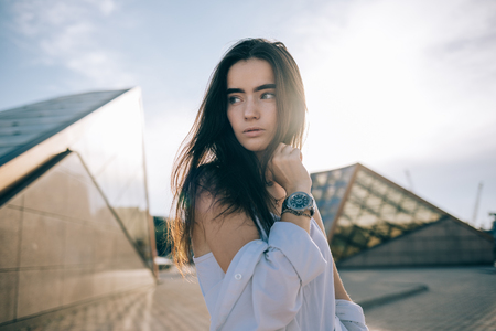 Beautiful young woman standing on the spacious street near the urban glass buildings looking to the side. Portrait of teen girl with long dark hair outdoors, sun shining through.