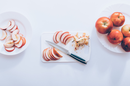 Slicing red apples on kitchen table, top view. Knife, cutting board next to plate with pieces and whole fruit on white background. Banco de Imagens