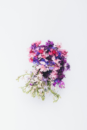 Bright bouquet of colorful cornflowers on white table, top view. Minimal floral flat lay arrangement, vertical framing.