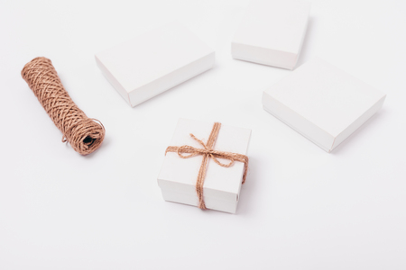 Packaging gifts jute rope. Minimalistic stylish composition of small gift box next to twine coil and simple white presents.