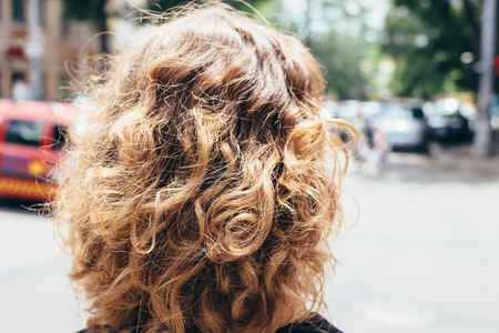 Woman's head with fluffy curly brown hair, back view. Close-up unrecognizable girl goes away at sunny day in the city.