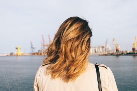 Close-up young woman looking at sea port standing on embankment. Female head with golden honey color wavy hair, rear view. Banco de Imagens