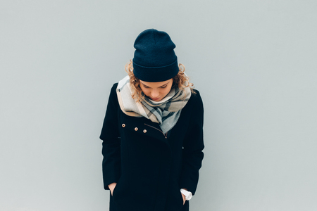 Jeune femme debout à l'extérieur par temps froid sur fond de mur bleu clair. Femme portant un manteau, un bonnet et une écharpe regardant vers le bas.