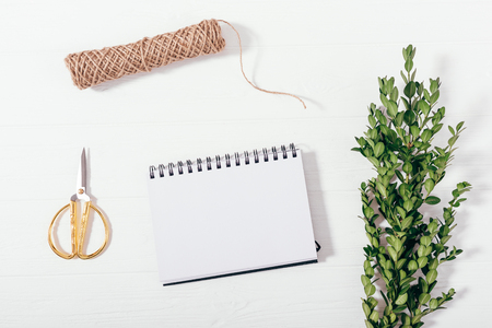 Flat lay composition preparation for the holiday. Mock-up blank notepad, gold scissors, twine and green branch, top view on white wooden table.
