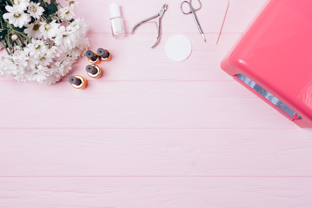 Feminine flatlay equipment long lasting manicure. Manicurist workplace on pink wooden desk. Set shellac covering: bottles gel nail polishes, ultraviolet lamp, tools and bouquet flowers, top view. Standard-Bild - 111079323