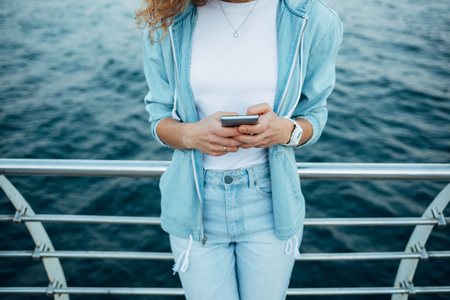 Young woman using smart phone standing on sea coast leaning on railing of embankment. Female dressed in jeans, jacket and white t-shirt holding mobile device on background of blue water, close-up.