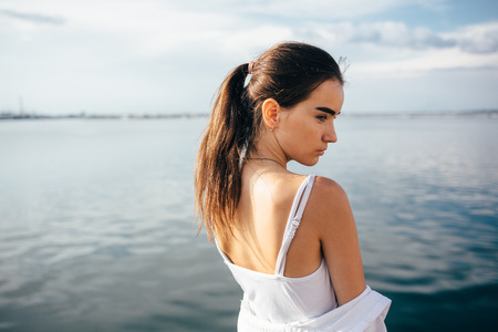 Side portrait of beautiful brunette young woman near the sea. Back view girl with ponytail hairstyle looking aside at sunny day.