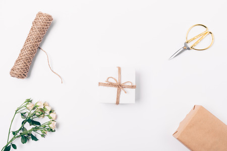 Flower arrangement of small present box, rose branch, twine and scissors, top view. Flat lay arrangement of decorative items for packaging gifts. 스톡 콘텐츠