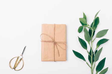 Minimal flat lay arrangement of fresh leaves and present wrapped in eco kraft paper. Gift box, scissors and green twig on white background, top view.