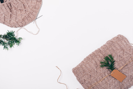 Flat lay frame handmade knitted wool sweater packed as gift near Christmas tree branch, top view on white background with empty space in central area. Stock Photo