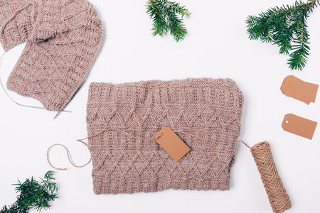Handmade wool sweater lies on white table amidst flat lay frame of fir branches and brown labels, top view.