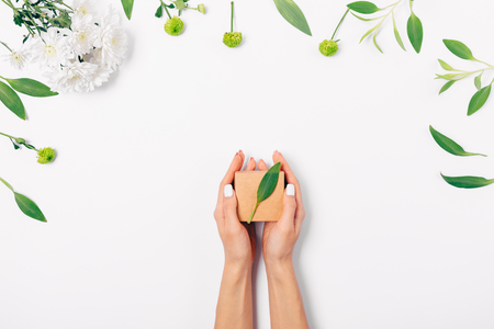 View from above womans hands holding small gift box of brown eco paper, flat lay composition of fresh flowers and green leaves on white background.