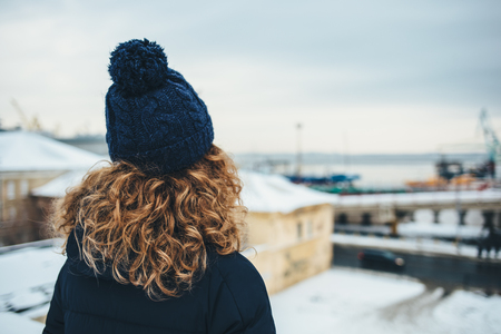Young woman with curly red hair wearing knitted hat looking at sea and city port on winter day, rear view.