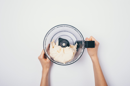Woman's hands holding bowl of food processor with ready kneaded dough on white table, top view.