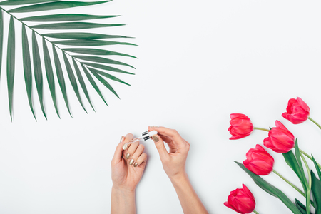 Woman's hands with gold manicure apply nourishing serum on cuticle and nails next to palm leaf and bouquet of flowers on white table, top view.