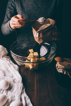 Close-up of female's hands holding bag and heaped spoon of flour pouring into bowl with diced butter to make dough for pie. Woman cooking homemade cake. Foto de archivo