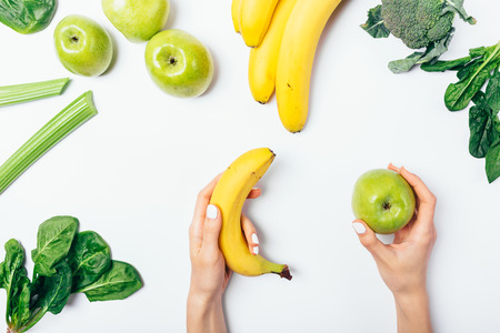 View from above womans hands holding apple and banana near healthy fresh fruits and vegetables: spinach, fresh celery and broccoli on white background, flat lay.