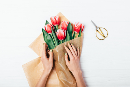 View from above female's hands wrapping bunch of red tulips next to golden scissors on white wooden table. Flat lay composition of woman making bouquet of fresh flowers in brown kraft paper. Foto de archivo