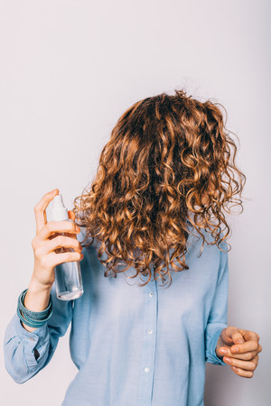 Young woman with long curly hair applying cosmetic care product. Female using spray with sea salt to make beachy waves hairstyle.