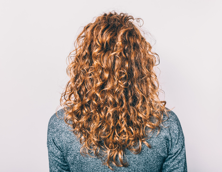 Rear view of young woman with long brown curly hair against plain background.