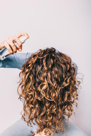 Der Kopf einer jungen Frau mit langen lockigen Haaren wird gesenkt, um ein kosmetisches Pflegeprodukt aufzutragen. Frau, die Spray mit Meersalz verwendet, um Strandwellenfrisur zu machen.