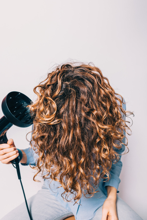 Close-up young woman sitting on chair styling her curly hair with hairdryer with special diffuser nozzle. Stock Photo