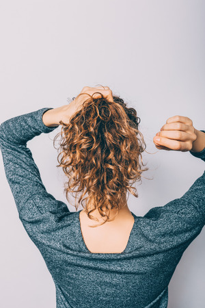 Rear view of young woman with curly hair doing her ponytail hairstyle.