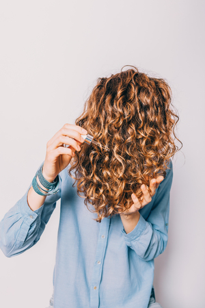 Unrecognizable young woman wearing blue shirt holding her curly brown hair applying nutritional cosmetic oil.