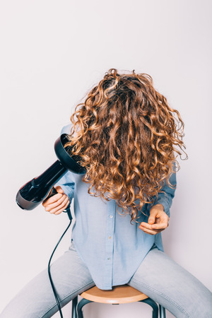Young woman sitting on chair styling her curly hair with hairdryer with special diffuser nozzle. Stock Photo