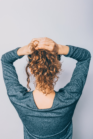 Back view of young woman with shiny curly hair making her ponytail hairstyle on white background.