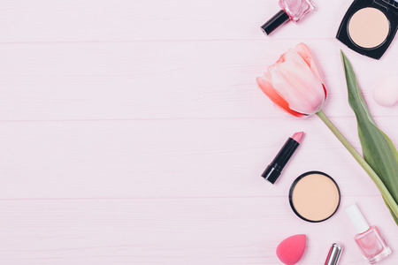 Makeup products and fresh tulip flower on pink table, top view. Festive flat layout of decorative women's cosmetics and accessories on wooden background with copy space for design.