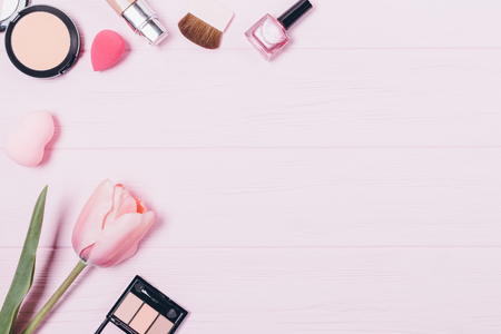 Feminine decorative cosmetics on wooden table, top view. Flat lay composition of beauty products and accessories, copy space.
