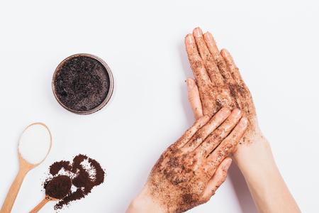 Las manos femeninas aplican movimientos de masaje exfoliante cosmético de café molido, azúcar y aceite de coco, vista superior en la mesa blanca
