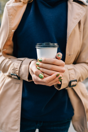 Womans hands with green manicure holding cup of hot coffee outdoors, close-up.