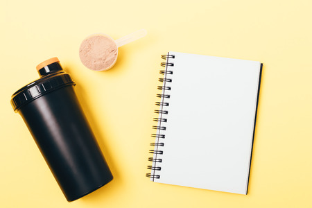 Personal protein shaker and powder in measuring spoon near blank white notepad on yellow background, top view. Stockfoto