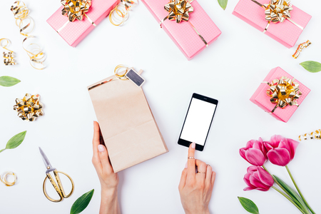 Flat lay composition of female's hands holding paper bag and touching blank smart phone display among gift boxes, pink tulip flowers and golden decorations on white table, top view.