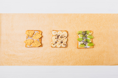 Flat lay composition ideas for tasty healthy breakfast. Different fruit toasts on cooking paper, top view. Imagens