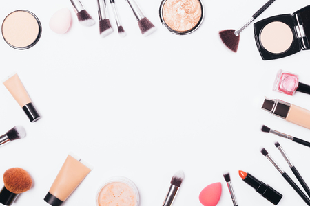 Decorative cosmetics and accessories on white background with empty space for text. Makeup products and tools, top view.