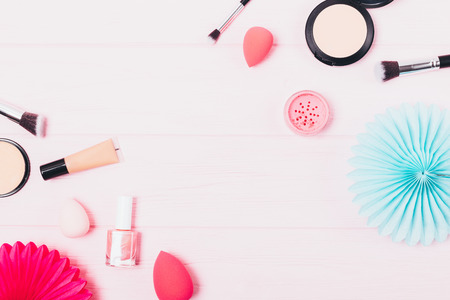 Flat lay frame of feminine cosmetics and makeup accessories on pink background with blank space in center.