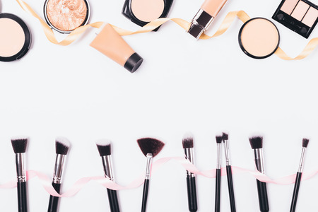 Make-up background of cosmetics for even complexion and professional brushes, top view. Flat lay frame of beauty products and accessories on white table with empty space in middle.