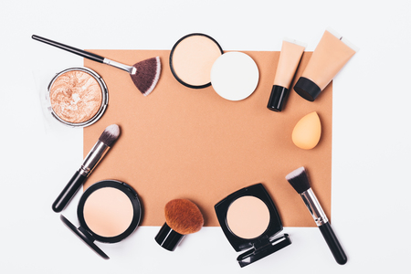 Cosmetics for correction of facial skin imperfections and accessories for its application on white table, top view. Flat lay frame of makeup products and brushes with sponges.