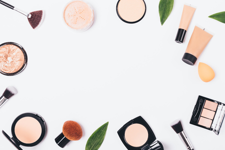 Flat lay a frame of makeup products and accessories on a white background with a blank space in center, top view.