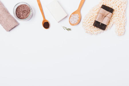 Homemade anti-cellulite beauty products and accessories on white background, flat lay. View from above composition of coffee scrub with sea salt, soap bars and massage mitten.
