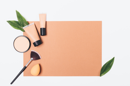 Makeup products flat lay frame on brown paper with copy space. Foundation, concealer and powder next to the sponge and brush for application, top view.