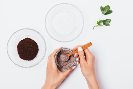 Top view female making homemade coffee scrub with sea salt and coconut oil. Woman's hands holding jar and spoon near ingredients for natural cosmetic on white background, flat lay. 版權商用圖片