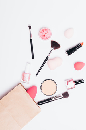 Women's makeup products flowing from brown paper shopping bag on white background, flat lay.