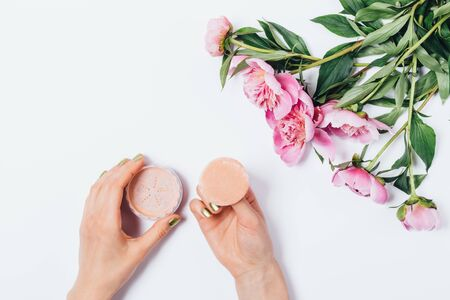 Top view woman's hands holding makeup puff applicator with loose beige facial powder near fresh bouquet of pink peonies on white background, flat lay. Imagens